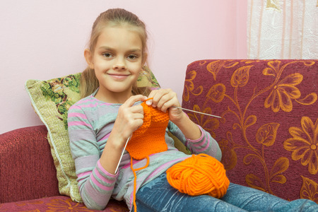 looked: Girl sitting on the couch, knits on the needles, and looked into the frame