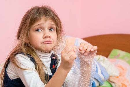 Rozrušená dívka trápící tváře požívá bublinky obalového filmu a hledá někoho