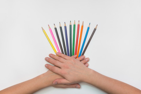 On a sheet of paper spread out like a fan of pencils, womens hands, palms lie on them Stock Photo