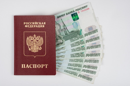 Passport and money fanned out on a white background
