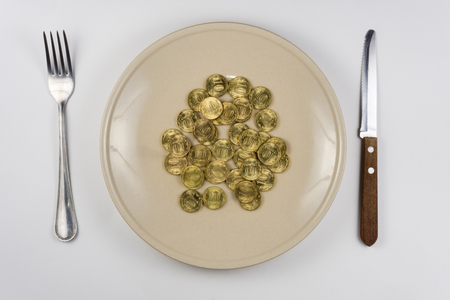 On the plate is a bunch of Russian ten-coin lying near tableware view from above