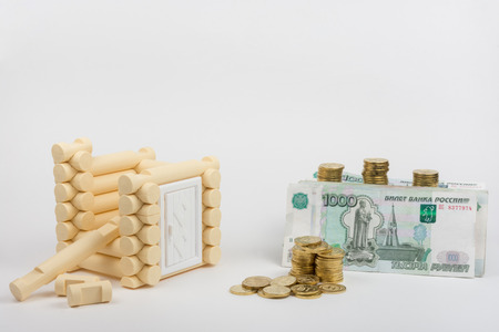bill of rights: Unfinished toy house, next are Russian rubles banknotes and coins Stock Photo