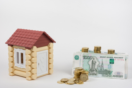 buying a home: Near the toy house is a lot of money on buying a home, white background