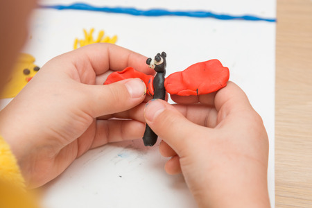 blinded: Child sculpts from clay butterfly, close-up Stock Photo