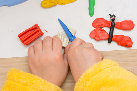 blinded: The child cuts off a piece of plasticine stack, close-up