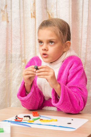 Seven-year girl looked up thoughtfully engaged in modeling of plasticine