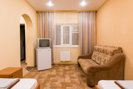 The interior of a small room with sofa bed and two single beds, window, TV and fridge