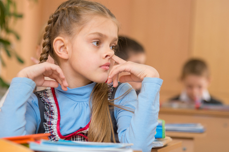 The girl at a lesson at school picking his nose
