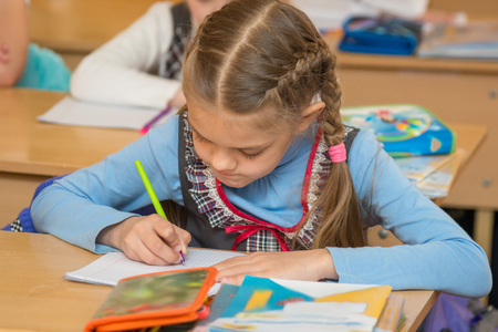 First-grader at a lesson of mathematics to solve the examples notebook Stock Photo