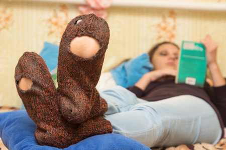 The girl is lying on the couch and is reading a book, in the foreground the holey socks Stock Photo