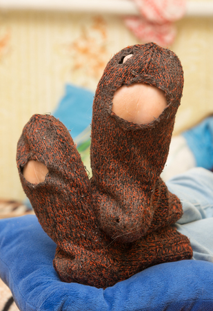 Woolen socks with huge holes on the legs of a man Stock Photo