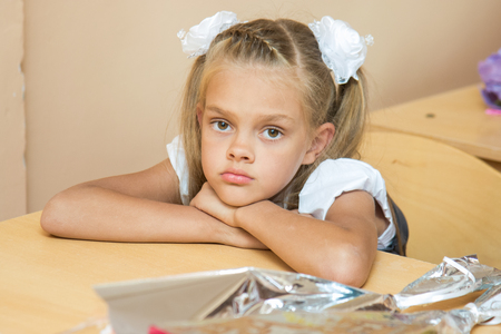 A sad girl at her desk at the lesson of the first of September Stock Photo