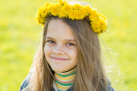 Portrait of a happy eight-year-old girl with a wreath of dandelions on her head, against the background of a spring clearing