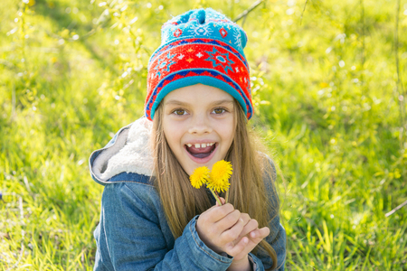 Seven-year-old girl in the spring is pleased with the blossoming dandelions Stock Photo