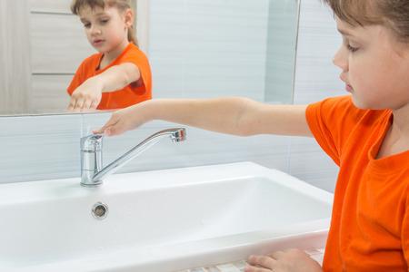 La ragazza ha chiuso l'acqua dal miscelatore dopo il lavaggio