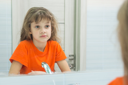 Seven-year-old girl looks at herself in the mirror, in the bathroom