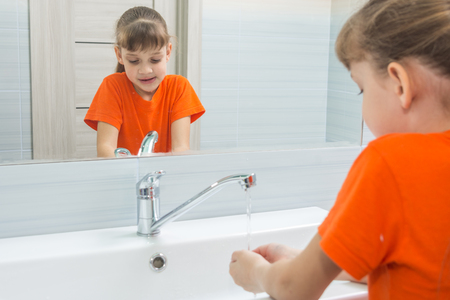 Seven-year-old girl washes face in bath