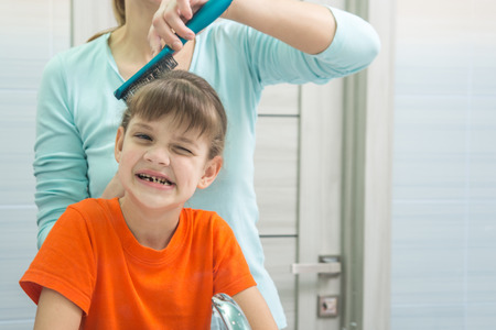 Mom combs her seven-year-old daughter in the bathroom Stock Photo