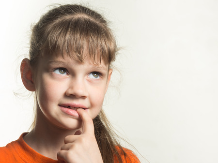 Portrait of a shy girl with a finger in her mouth, looking up thoughtfully