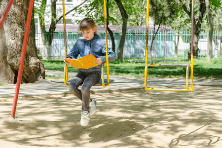 A girl on a walk reading a book swinging on a swing at the playground