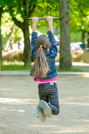 A girl is riding a metal ladder on chains in a playground
