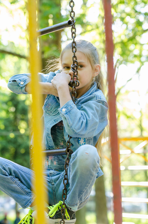 The girl pondered climbed the hanging ladder in the playground Фото со стока