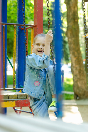 The girl joyfully and fervently laughs sitting on a hanging ladder in the playground Stock Photo