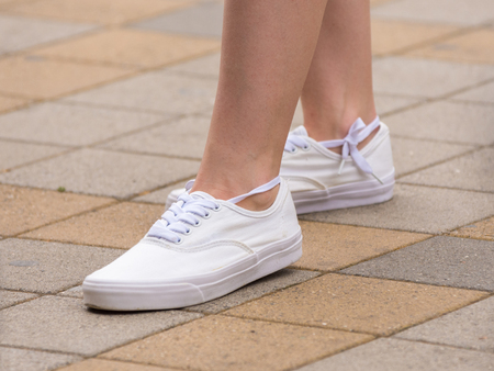Female sneakers are dressed on a girl, a girl is standing on the sidewalk Stock Photo