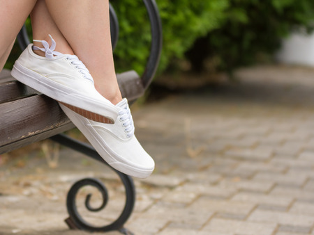 Female gym shoes close-up, the girl sits on a bench