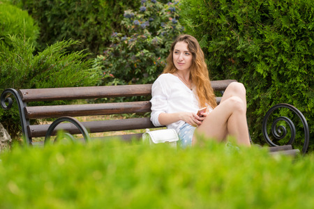 Young girl with phone in hands, sits on bench in park