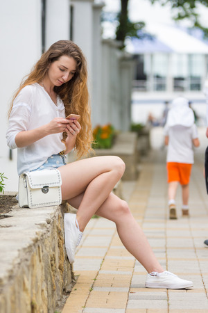 A young girl sitting on the fence of the flower bed, communicating in the phone with friends in social networks