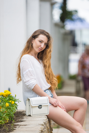 A young girl with a ladys white handbag crouched on the parapet and looked at the frame