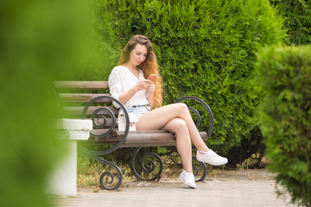 Young girl communicates in social networks sitting on a park bench