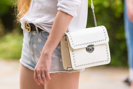 Stylish womens white handbag close-up on a girl