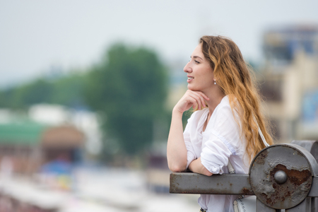 A young girl looks into the distance leaning on the old fence Stock Photo
