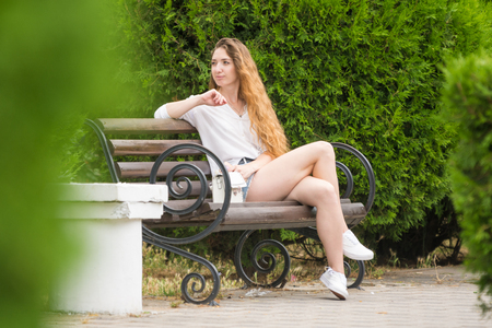 A young girl looks on the sides resting on a park bench
