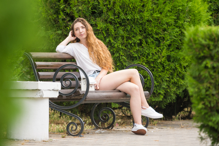 Young girl resting on a park bench Stock Photo