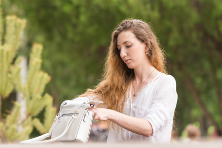 Beautiful young girl is delving into her purse in the park Stock Photo