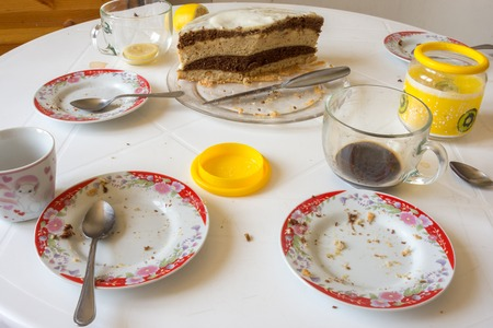Dirty dishes on the table, homemade cake in the background Stock Photo