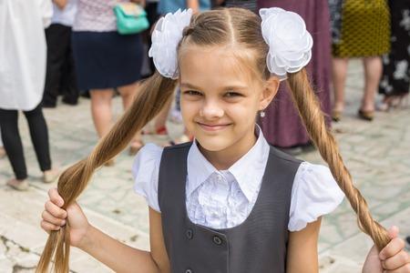Schoolgirl at the festival on September 1 holds her long hair in her hands Stock Photo