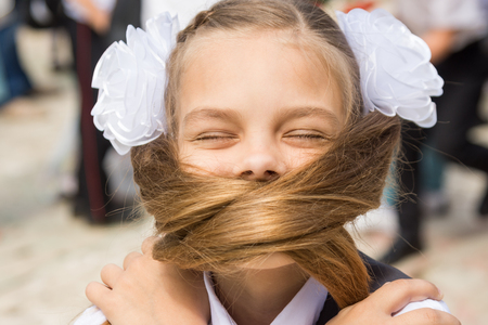 The schoolgirl on a holiday on September 1 covered her face with her long hair