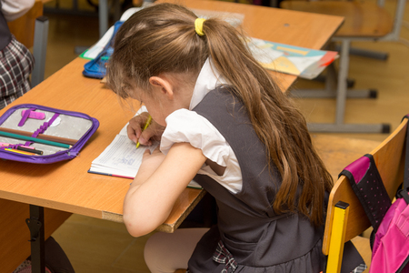 Schoolgirl with a wrong posture in class at school Stock Photo
