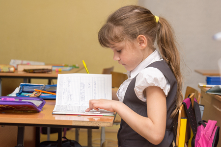 A little girl in a class carefully reads a diary entry