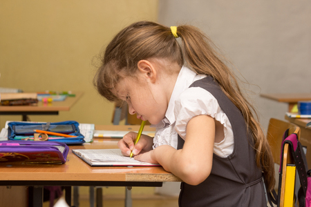 A schoolgirl in a lesson crouched writes in a notebook Stock Photo