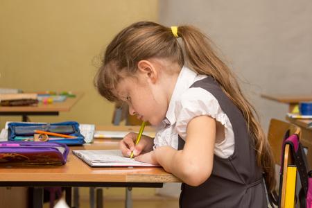Una studentessa in una lezione accovacciata scrive su un taccuino