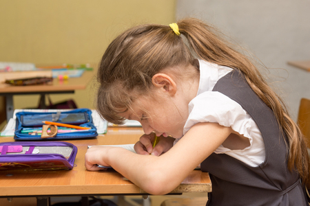 A schoolgirl with a wrong posture at the lesson writes in a notebook Stock Photo