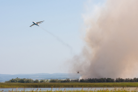 Extinguishing fire from the air using an airplane and a helicopter, with the burning of reeds on the floodplains of the Anapka River, Anapa, Russia
