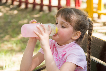 A girl on a bench on a hot day drinking water from a bottle Foto de archivo