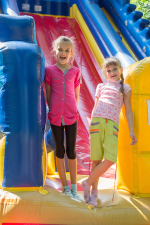 Two joyful girls stand at the entrance to a large inflatable trampoline