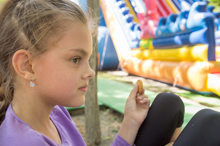 A girl in a trampoline park bites a liver on a bench